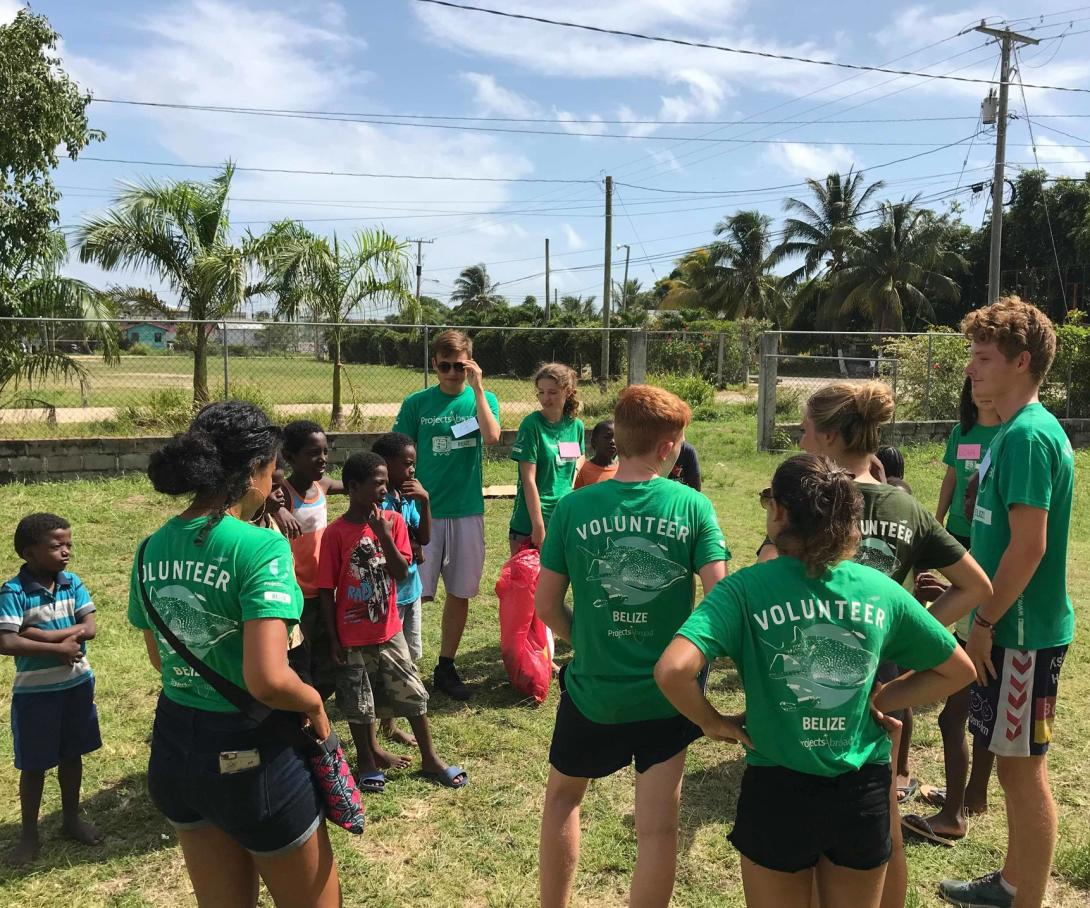 High school students volunteering in Belize explain a litter and recycling awareness activity to children at a summer camp.